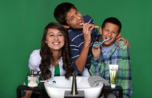 3 children,over sink- brushing teeth with Forever Bright tooth-gel