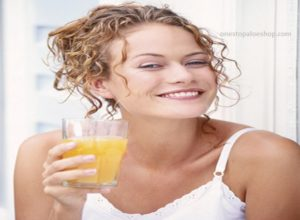 head-shot of pretty woman smiling and holding a glass of aloe gel
